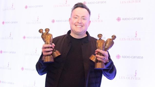 L'homme sourit en montrant ses trophées.