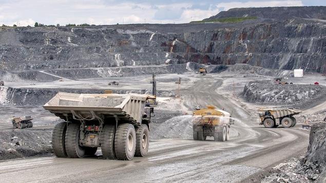 Au fond de la mine, des camions arrosent le sol.
