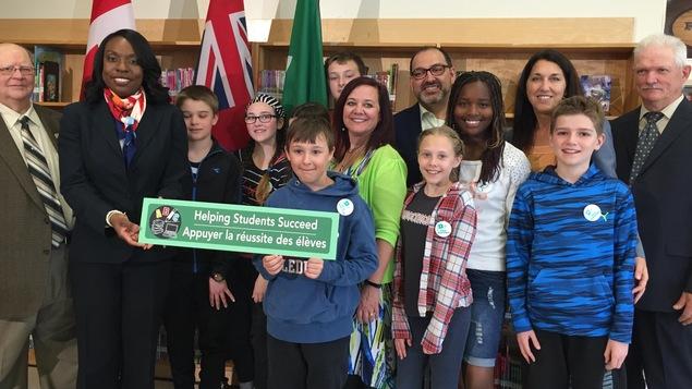 Les ministres Mitzie Hunter et Glenn Thibeault aux côtés d'élèves de l'école St-Dominique de Sudbury
