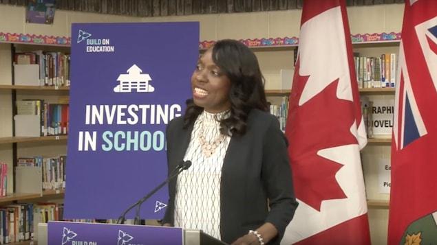 La ministre parle d'un podium dans une école
