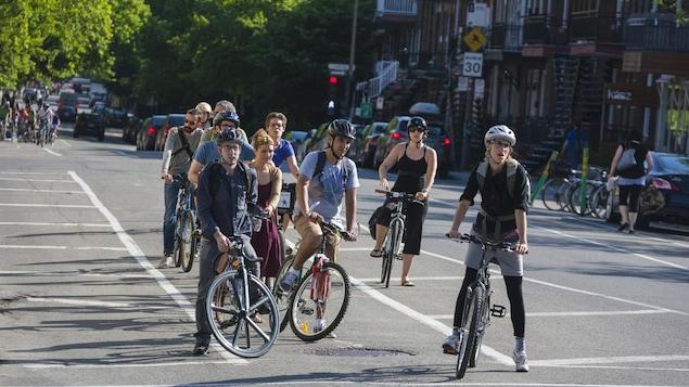 Des cyclistes attendent à une intersection.