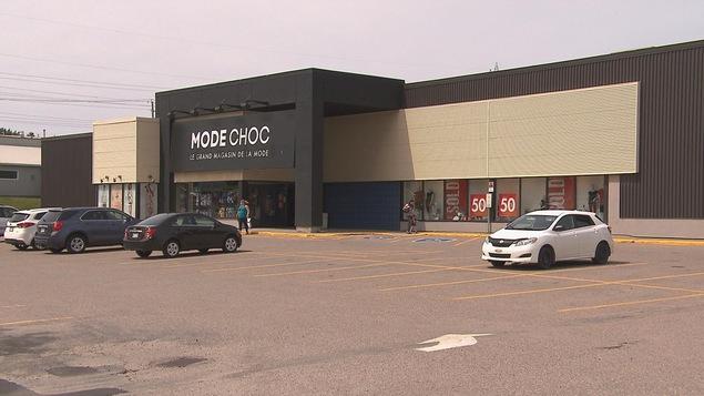 Le stationnement d'une boutique Mode Choc avec quelques voitures et clients.