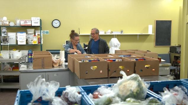 Deux personnes dans un entrepôt de denrées alimentaires.