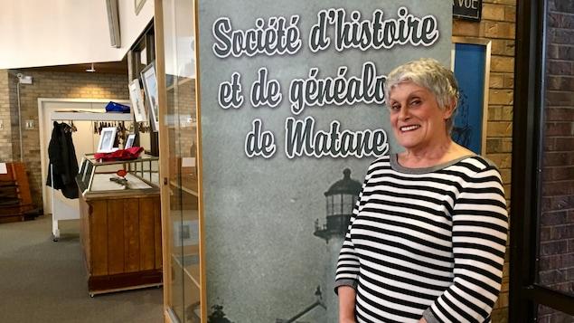 On voit Monique Fournier devant un panneau où il est écrit « Société d'histoire et de généalogie de Matane ».