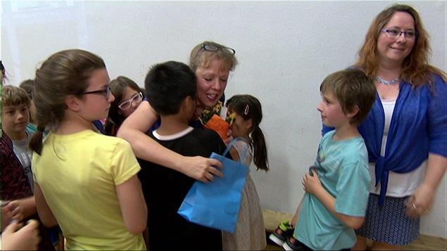 Des enfants enlacent leur enseignante en lui remettant des cadeaux,