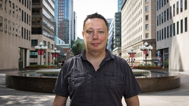 Une photo de Patrick Poirier, qui se tient debout devant une fontaine, au centre-ville de Montréal, entouré de gratte-ciels.