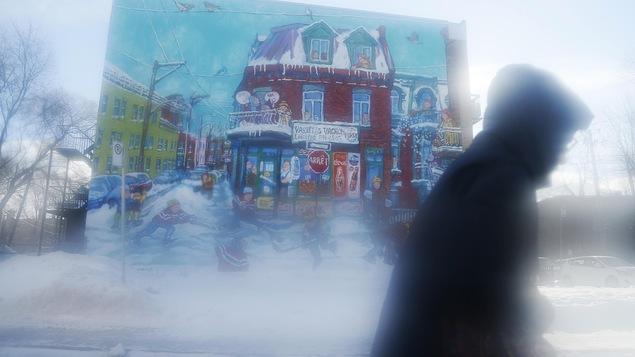 Un piéton marche lors d'une journée de tempête à Montréal.