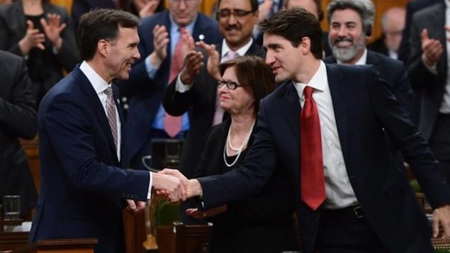 Le premier ministre Justin Trudeau, à droite, serre la main du ministre des Finances, Bill Morneau, après le dépôt du budget fédéral à la Chambre des communes mercredi.