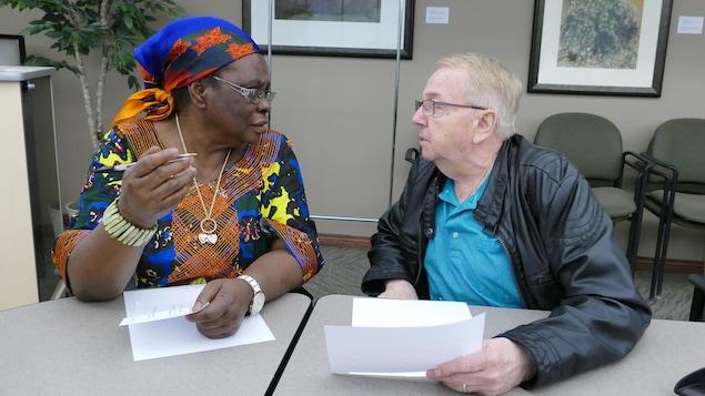Une femme noire parle avec un homme blanc.