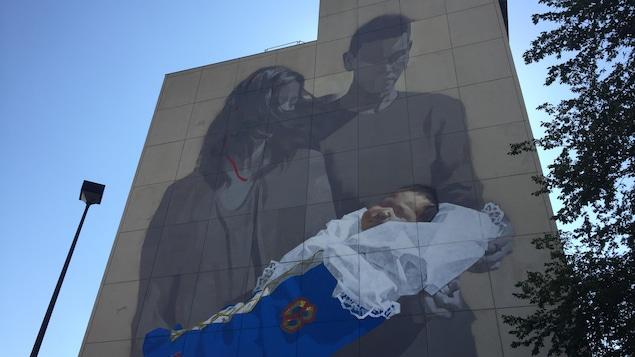 Une mère et un père tiennent un bébé emmailloté.
