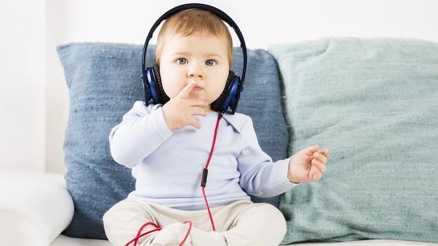 Un bébé écoute de la musique.