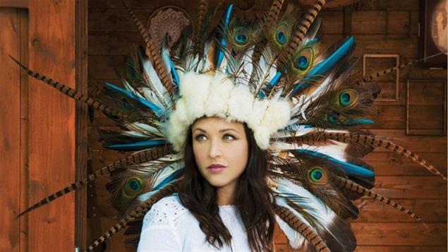 La chanteuse Natasha St-Pierre avec une coiffe ressemblant à une coiffe autochtone traditionnelle