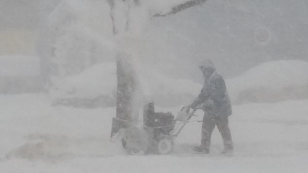 Une personne manie une souffleuse à neige dans la tempête.