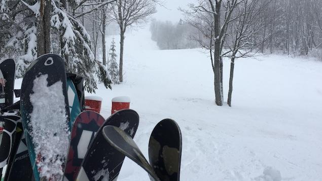 Des skis installés à la verticale, sur fond de piste de ski enneigée