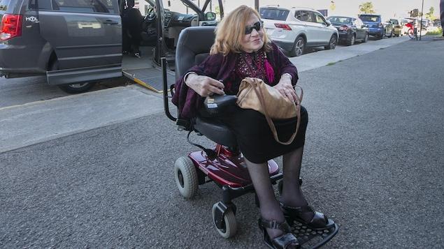 Nicole Gladu dans son fauteuil roulant à l'extérieur.