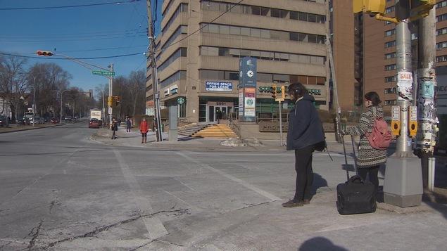 Des piétons attendent de traverser la rue à Halifax.