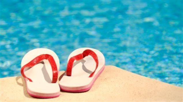Des sandales sur le bord d'une piscine