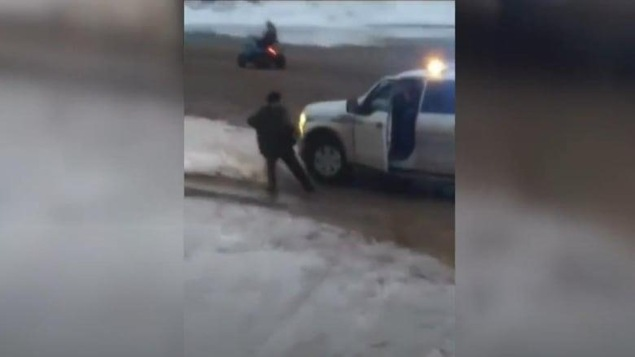 Une saisie d'écran d'une vidéo montrant l'arrestation d'un homme par un agent de la Gendarmerie royale du Canada à Kinngait, au Nunavut.