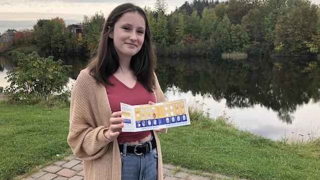 Une adolescente montre sa plaquette de médicament. Elle pose devant une rivière, en automne.