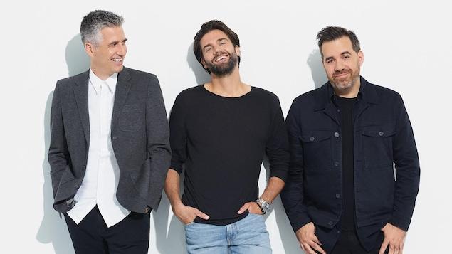 Les trois hommes sourient, deux regardent la caméra.