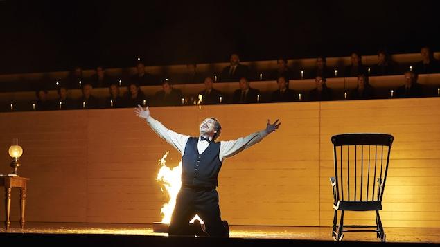 Russel sur la scène, agenouillé et les bras en l'air