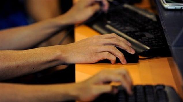 Des mains sur des claviers et une souris d'ordinateur