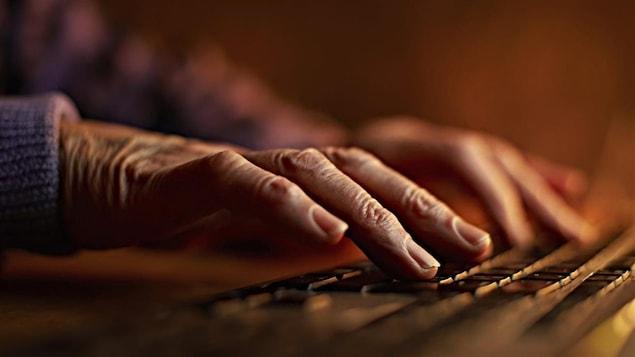 Un internaute tape sur un clavier d'ordinateur.