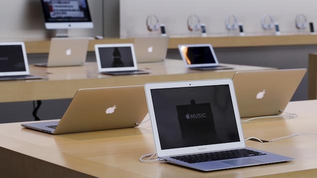 Plusieurs ordinateurs portables de la marque Apple sont disposés sur des tables.