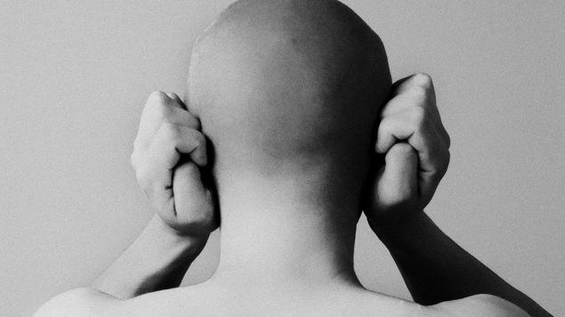 Une personne vue de dos couvre ses oreilles avec ses mains.