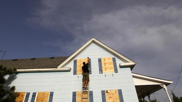 Un résident de Cape Hatteras, en Caroline du Nord, se prépare au passage de l'ouragan Irene, en août 2011, en barricadant les fenêtres de sa maison.