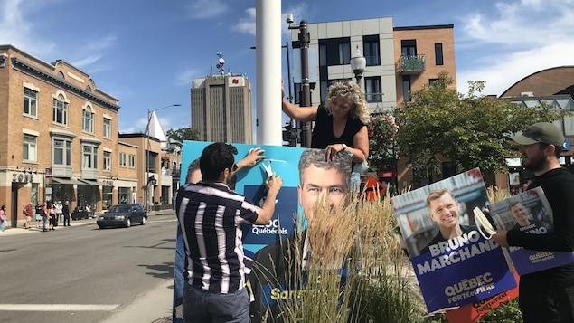 Un militant coupe l'attache d'un pancarte du candidat bloquiste Louis Sansfaçon.