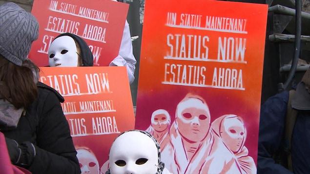 Une pancarte demandant que le statut des femmes sans-papiers soit régularisé.