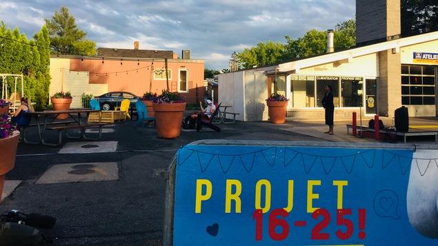 Une affiche sur laquelle est écrit « Projet 16-25 » devant des tables à pique-nique et des chaises de jardin.