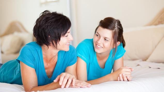 Une mère et son adolescente sont étendues sur un lit et se regardent en souriant.