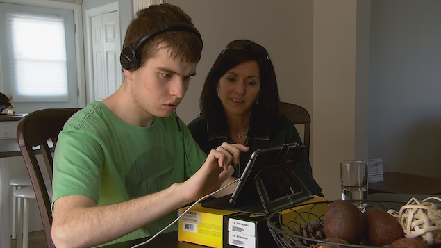 Chantal Belley regarde son fils Olivier utiliser une tablette informatique.