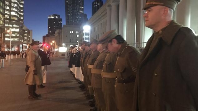 Une vingtaine de personnes habillées en soldats et en infirmières devant la gare Union.