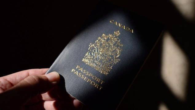 Une main tend une passeport canadien.
