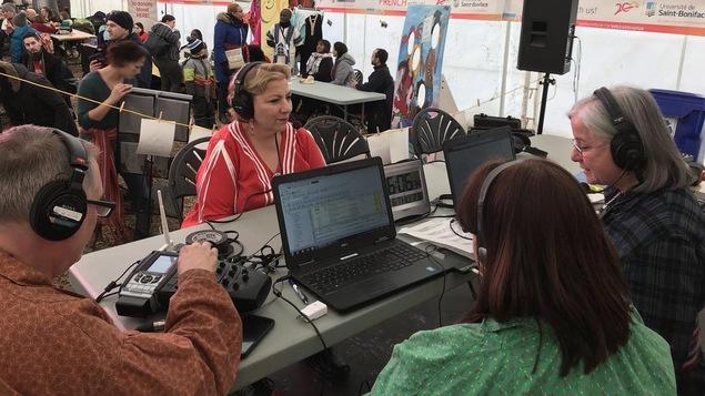 Assise devant une table, Paulette porte un chandail rouge et blanc, elle fait face à l'équipe de l'émission: Animatrice, technicien et journaliste.