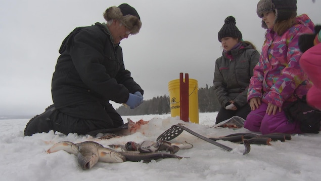 Un grand-père montre à ses deux petits-enfants quelques trucs pour la pêche sur glace
