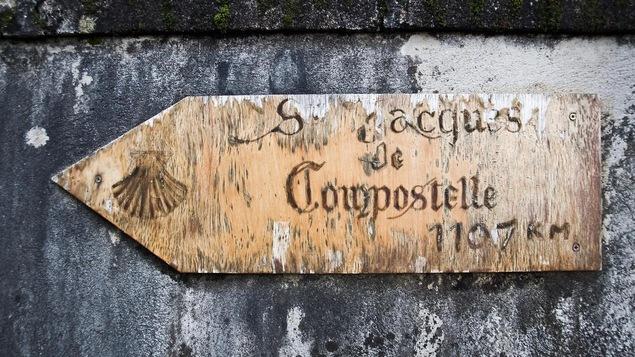 Un panneau en bois indiquant le chemin de Saint-Jacques-de-Compostelle