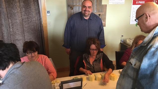 Le père Patrick McGraw au milieu des bénévoles qui vendent les billet de loterie.