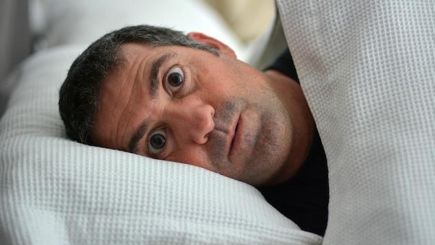 Un homme est couché dans un lit, les yeux grands ouverts.