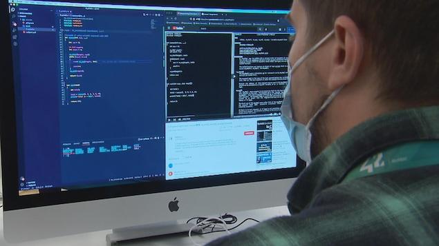 Un homme devany un ordinateur.