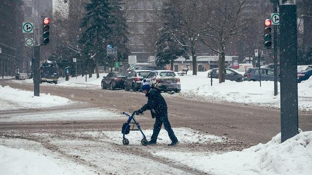 Un piéton traverse la rue en s'appuyant sur son déambulateur, dans une rue enneigée du centre-ville de Montréal.