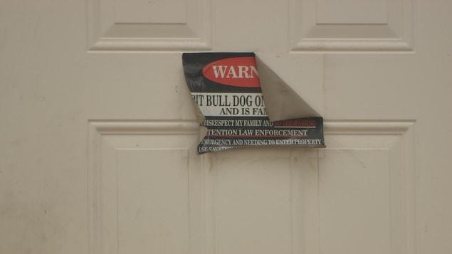 Une affiche qui met en garde contre les pitbulls se retrouve sur la porte du propriétaire de l'animal qui a blessé la chienne Callie à deux reprises.
