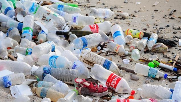 Des déchets et plusieurs bouteilles de plastique vides jonchent le sol d'une plage en Malaisie.