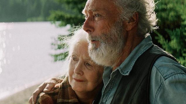 Un couple agé se serre près d'un lac.
