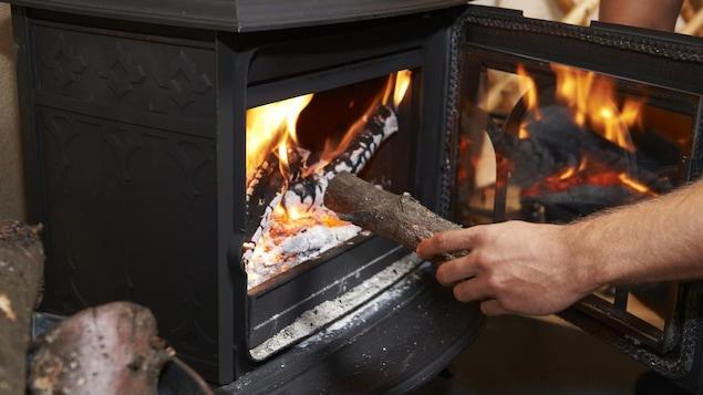 Une personne met une bûche dans un poêle à bois.