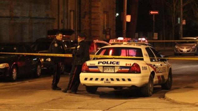Des policiers et une voiture de police garée dans une rue la nuit. Un périmètre de sécurité est érigé.