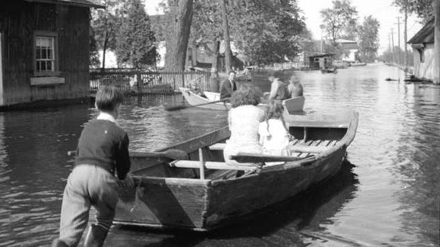 Une photo en noir et blanc illustre une barque qu'un garçon pousse dans une rue inondée.